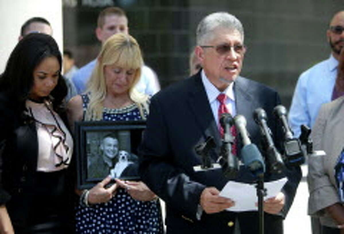 """Attorney U.A. Lewis, left, with Diane Jacobs, holding a photo of her son Jesse Jacobs, while her husband, also named Jesse Jacobs, announces they have filed a federal lawsuit against Galveston County at the United States District Court Southern District Monday, March 14, 2016, in Houston, Texas. The Galveston County Medical Examiner determined Jesse's cause of death to be """"abrupt discontinuation of long term alprazolam medication."""" Jesse died one year ago today. He went to jail to serve out a short sentence."""