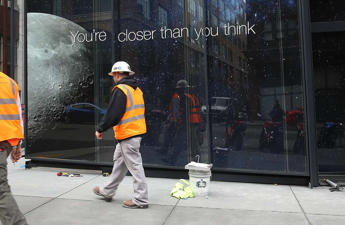 Construction workers pass the outside of the new LinkedIn headquarters at 222 2nd St. in San Francisco, California, on Monday, march 14, 2016.