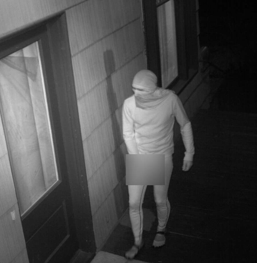 Seattle police seek this man, suspected of masturbating multiple times outside a University District home. He was caught on surveillance footage Feb. 7 wearing all black (which appears white in the image), including a wrap around his face and head and toe shoes.