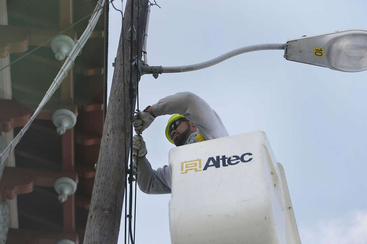 In this file photo, Mark Fa'aita, Department of Technology electrical line worker, tightens a pin holding fiber optic cable along Moulton Street on Monday, March 14, 2016 in San Francisco, California.