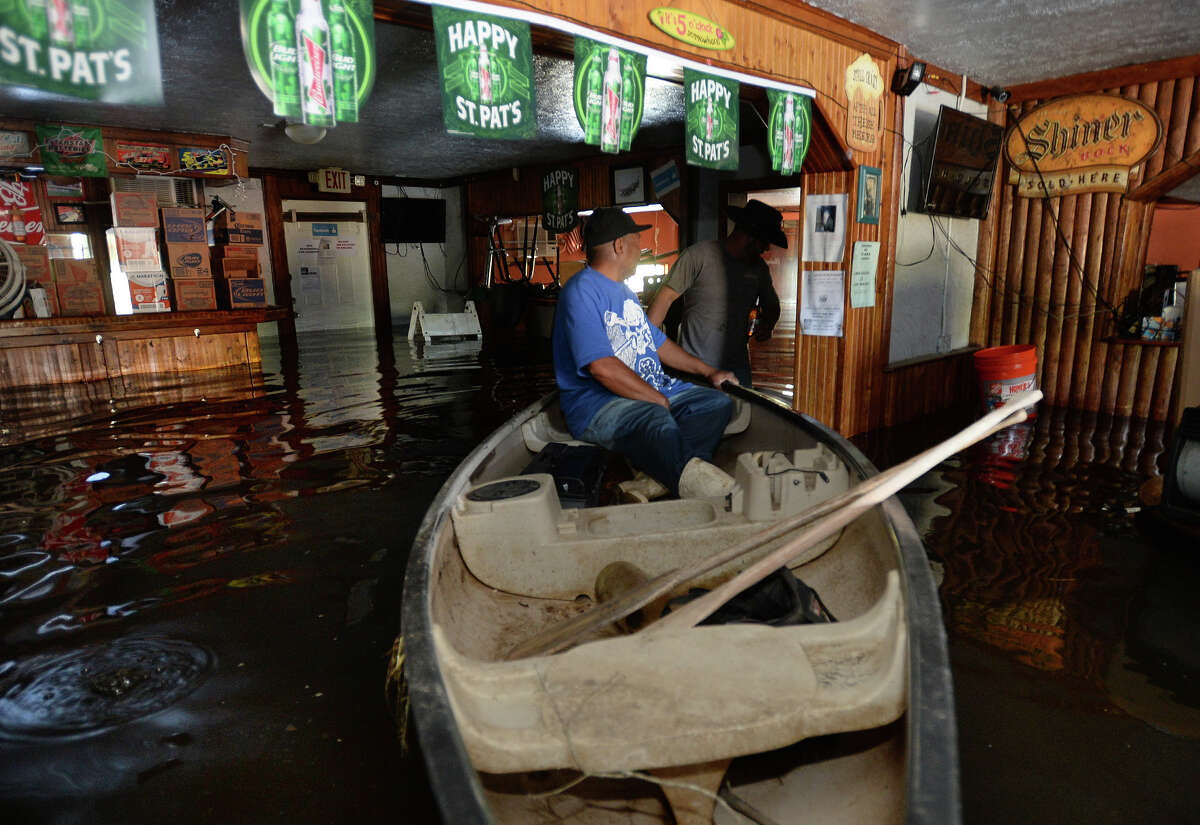 James Sparkman pulls Gerald Evans in a canoe through the flooded Bayou Club in Orange on Monday. Tasked with removing a jukebox, Evans used the canoe to get to the jukebox. Water from the nearby Bayou rose early Monday morning due to last week's rain. Photo taken Monday, March 14, 2016 Guiseppe Barranco/The Enterprise