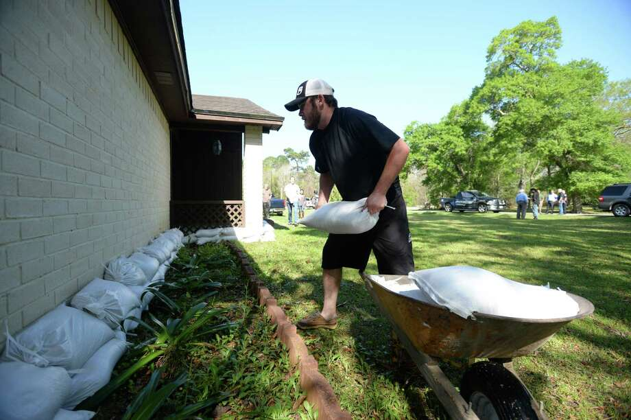 Paul Fregia piles sandbags along his girlfriend's family home in Pinehurst on Monday. Water from the  Water from the nearby Bayou rose early Monday morning due to last week's rain. Photo taken Monday, March 14, 2016 Guiseppe Barranco/The Enterprise Photo: Guiseppe Barranco, Photo Editor