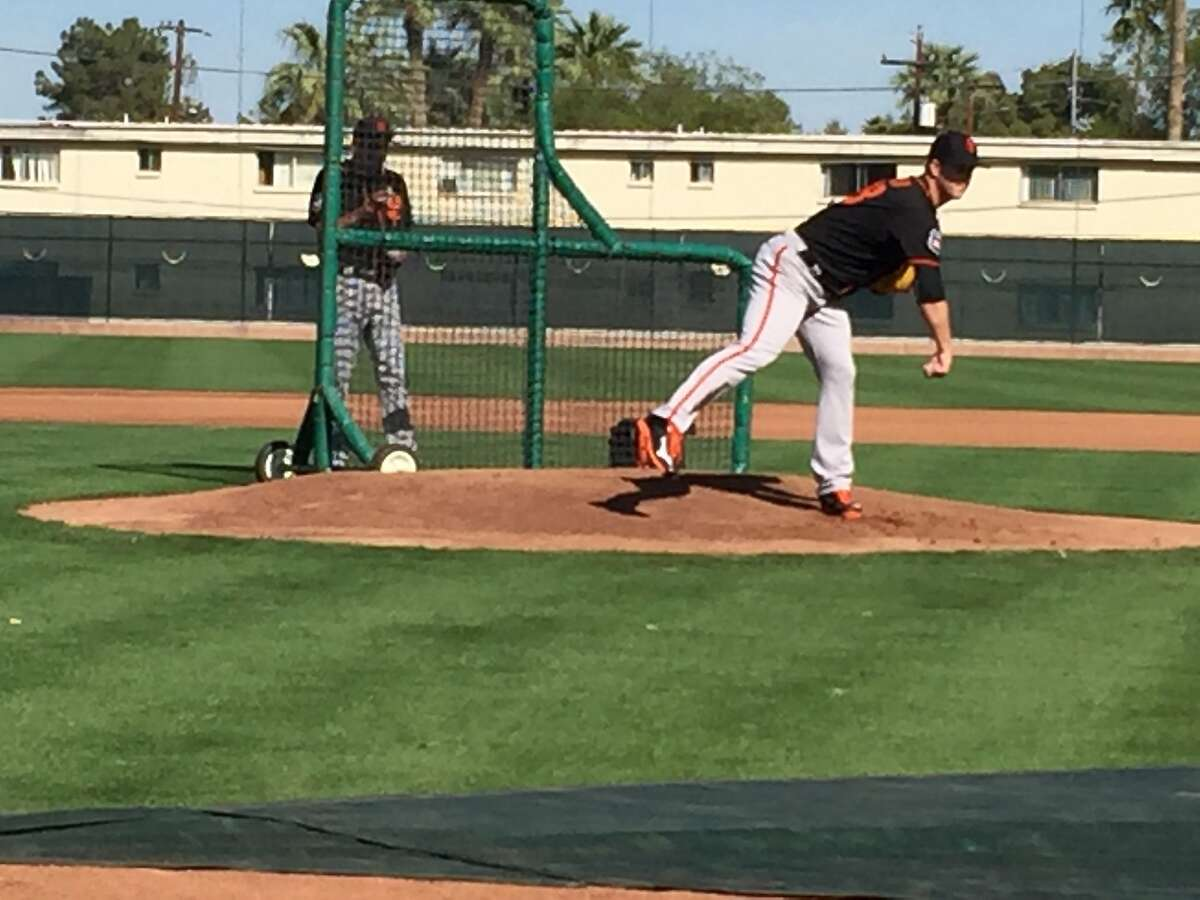 Matt Cain throws during a simulated game at Scottsdale Stadium, with pitching coach Dave Righetti watching.
