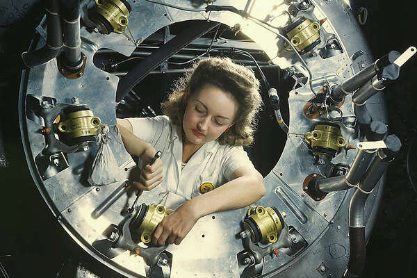 """Original caption reads: """"Part of the cowling for one of the motors for a B-25 bomber is assembled in the engine department of North American [Aviation, Inc.]'s Inglewood, Calif., plant."""" Photo dated October 1942, by Alfred T. Palmer."""
