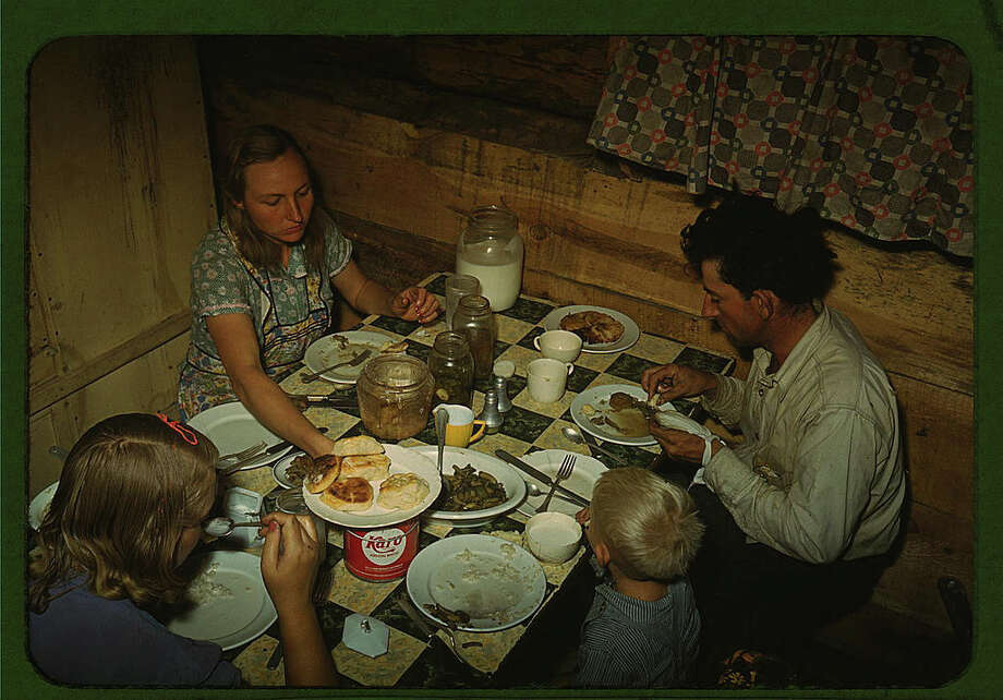 "Original caption reads: ""The Faro Caudill [family] eating dinner in their dugout, Pie Town, New Mexico."" Photo dated October 1940, by Russell Lee. Photo: Farm Security Administration — Office Of War Information Collection, Library Of Congress / 2016 Public Domain"