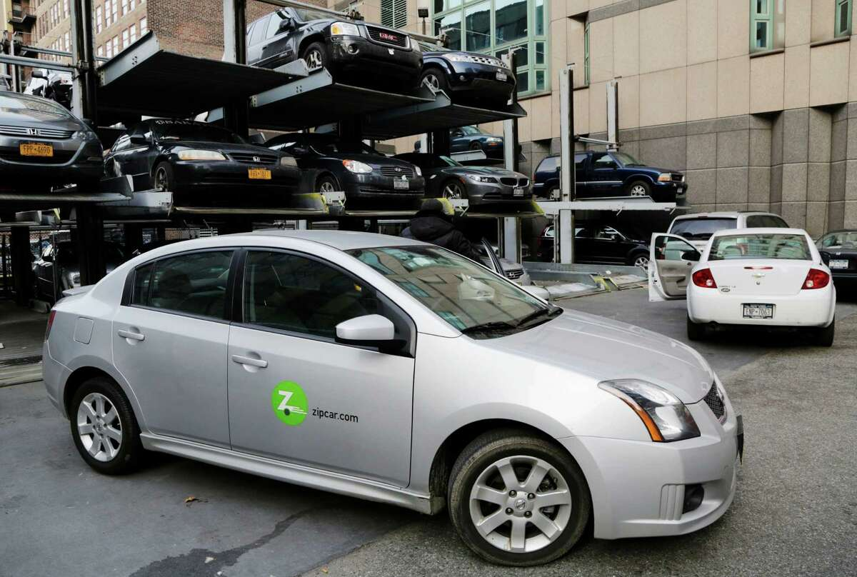 A Zipcar is parked at a lot, Wednesday, Jan. 2, 2013 in New York. Avis is buying Zipcar for $491.2 million, expanding its offerings from traditional car rentals to car sharing services. (AP Photo/Mark Lennihan) ORG XMIT: NYML109