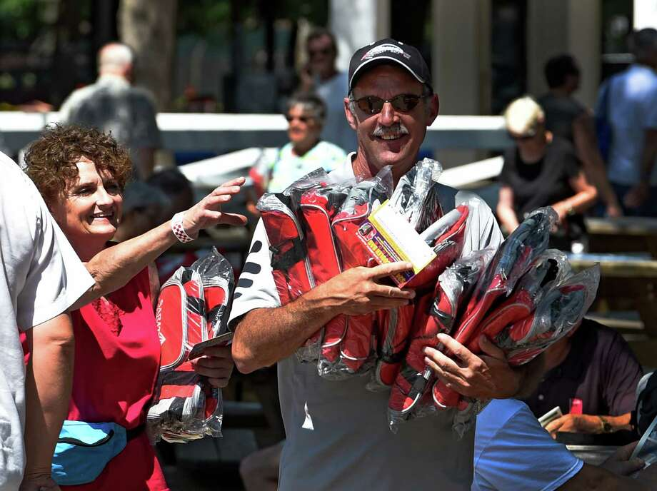 Kerri Abela, left, helps Harold Rockefeller, both of Germantown, with his haul of cooler bags, the most recent giveaway of the Saratoga season Monday morning, Aug. 3, 2015, at Saratoga Race Course in Saratoga Springs, N.Y.  (Skip Dickstein/Times Union archive) Photo: SKIP DICKSTEIN / 10032868A