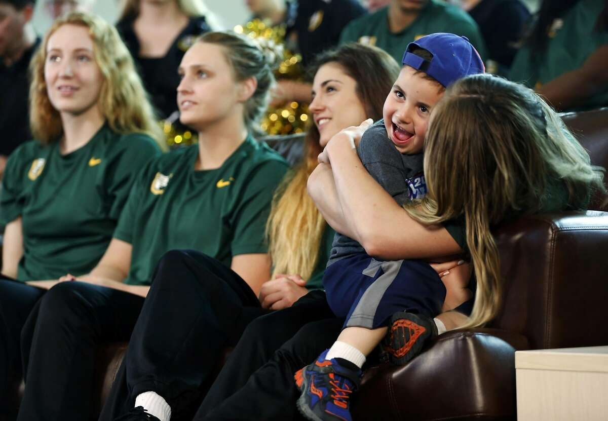 Ari Greenfield, 4, gets held by his babysitter and USF Women's Basketball player Taylor Proctor during a viewing party for the NCAA Women's Basketball tournament seeding at War Memorial at the Sobrato Center at USF in San Francisco, California, on Monday, March 14, 2016.