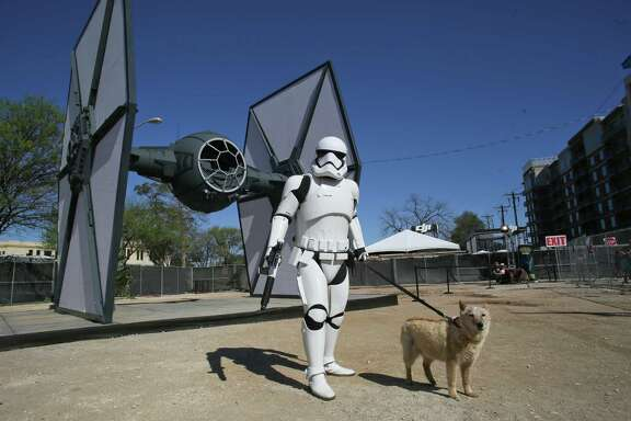 "Matilda the dog has her photo taken with a storm trooper in front of a to-scale ""Star Wars"" TIE fighter Sunday during the South by Southwest Film Festival. Disney set up the display to promote the documentary ""Secrets of The Force Awakens: A Cinematic Journey"" screening at the event."