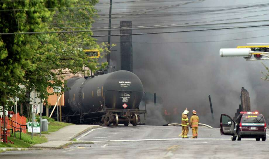 Smoke rises from railway cars that were carrying crude oil after derailing in downtown Lac Megantic, Quebec, Canada, Saturday, July 6, 2013. The derailment sparked several explosions and forced the evacuation of up to 1,000 people. (AP Photo/The Canadian Press, Paul Chiasson)  ORG XMIT: PCH102 Photo: Paul Chiasson / The Canadian Press