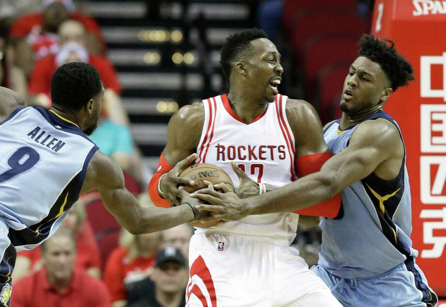 Dwight Howard is guarded by the Grizzlies' Tony Allen, left, and Alex Stepheson. Howard was one of only three Rockets not to score in double figures. Photo: Pat Sullivan, STF