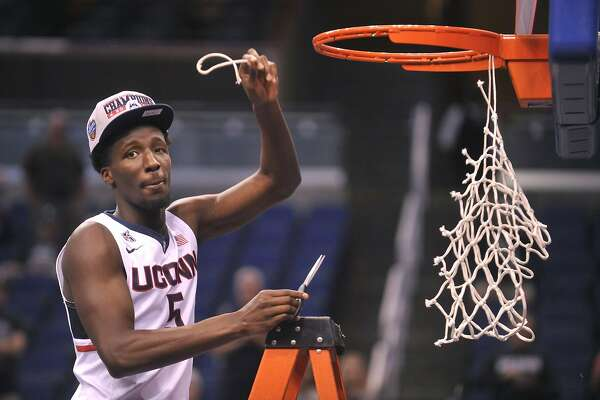 American Athletic Conference Championship's Most Outstanding Player Daniel Hamilton cuts down the net on Sunday, March 13, 2016, at the Amway Center in Orlando, Fla. UConn beat Memphis 72-58 to claim the conference title. (Brad Horrigan/Hartford Courant/TNS)