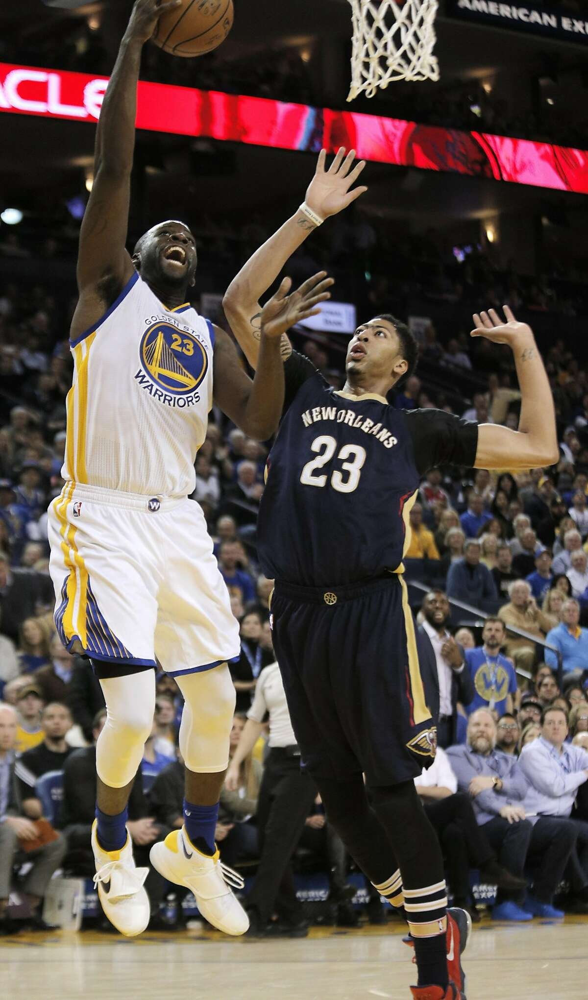 Draymond Green (23) puts in a layup over Anthony Davis (23) in the first half as the Golden State Warriors played the New Orleans Pelicans at Oracle Arena in Oakland, Calif., on Monday, March 14, 2016.