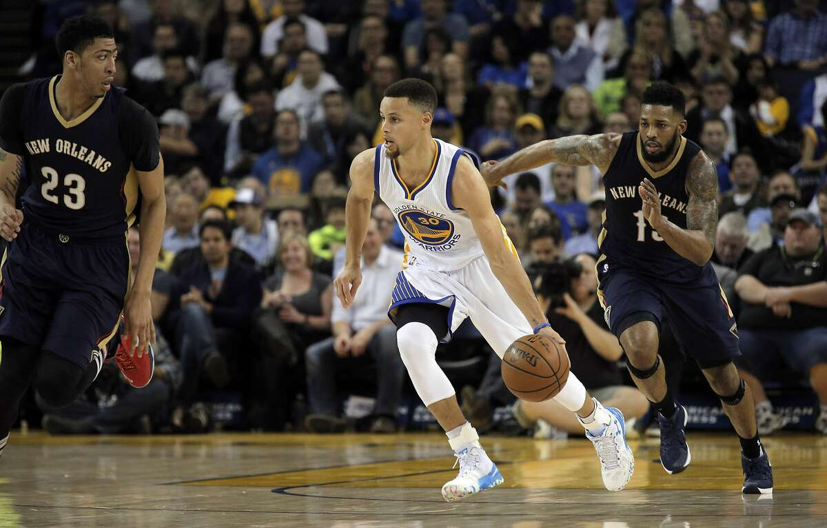 Stephen Curry (30) dribbles up the court in the first half as the Golden State Warriors played the New Orleans Pelicans at Oracle Arena in Oakland, Calif., on Monday, March 14, 2016.