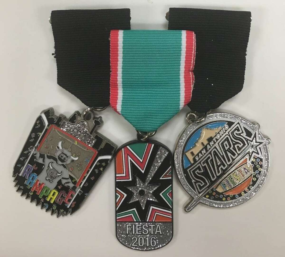 The 2016 Spurs Fiesta medal (center) along with the official Rampage and Stars medals.