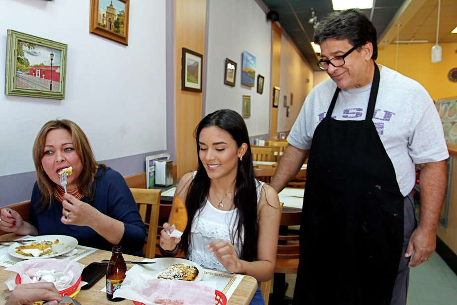 Budare Arepa Express at 402 West Grand Parkway South has many customers who share owner Manuel Vega's Venezuelan heritage. Vega, right, watches as Carmen Nunez, left, and Erica Rodriguez eat traditional dishes. Photo: Suzanne Rehak, Freelance Photographer