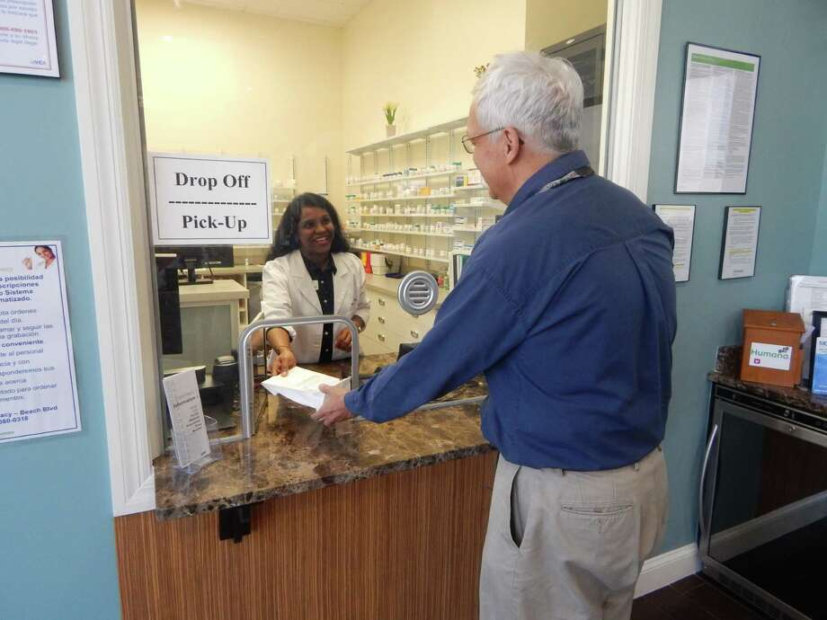 Humana has opened its second retail pharmacy in Texas at the MCCI Medical Group De Leon practice on San Antonio's South Side. Humana pharmacist Sunila Philipose (left) filled a prescription for a Humana customer at a similar retail pharmacy the insurer opened in Jacksonville, Florida last year. Photo: Courtesy Photo /Humana