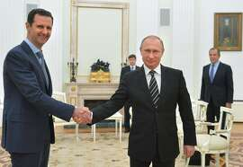 FILE - In this file photo taken on Tuesday, Oct. 20, 2015, Russian President Vladimir Putin, center, shakes hand with Syrian President Bashar Assad as Russian Foreign Minister Sergey Lavrov, right, looks on in the Kremlin in Moscow, Russia. Syria's state news agency is quoting President Bashar Assad as saying that the Russian military will draw down its air force contingent from Syria but won't leave the country altogether.(Alexei Druzhinin, Sputnik,  Kremlin Pool Photo via AP, File)