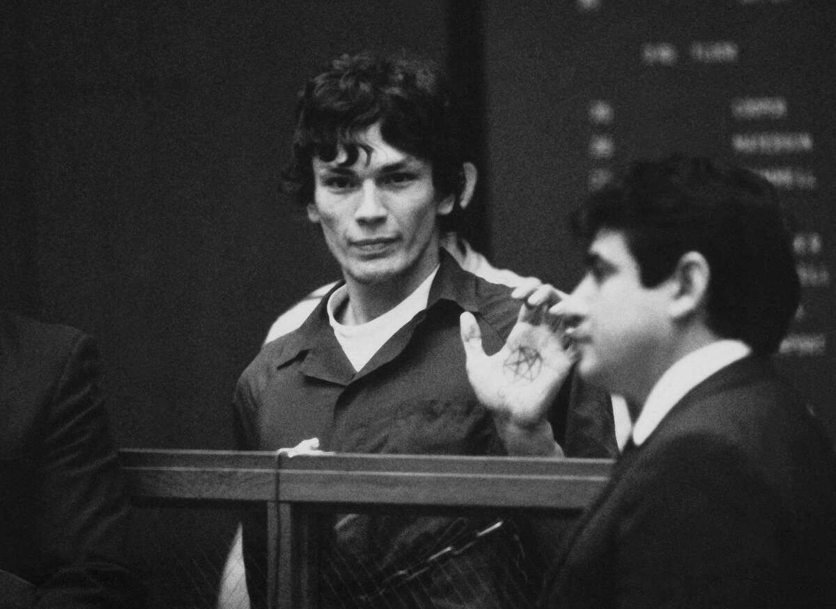 FILE-This 1985 file photo shows Richard Ramirez, center, know as the Night Stalker shows a pentagram on the palm of his hand in court. California corrections officials say convicted serial killer Ramirez, known as the Night Stalker, has died in prison. San Quentin State Prison spokesman Lt. Sam Robinson says Ramirez died Friday, June 7, 2013. . The man on the right is unidentified. (AP Photo,File)