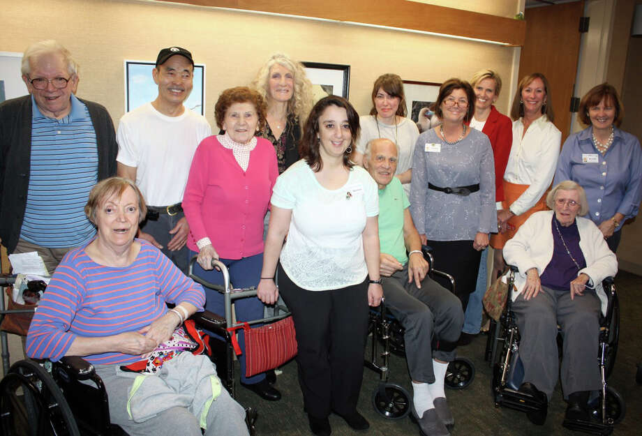 """A selection of works from the Carriage Barn's recent """"For the Birds"""" exhibit is now on display in the Waveny LifeCare Network's front lobby for residents, patients, families and guests to enjoy. Pictured from Waveny are Joe, Hope, Rose, Jerry and Gloria. Also,Waveny's director of volunteers Debbie Perron; Waveny therapeutic recreation staff, music therapist Sherrye Dobrin; art therapist Brenda Jacobsen; New Canaan Society for the Arts members and exhibiting artists Kiyoshi Otsuka and Dawn Kraemer; Carriage Barn Executive Director Valerie Garlick; NCSA President Serena Gillespie; and NCSA Trustee and Waveny Board member Sharon Stevenson. Photo: Contributed / Hearst Connecticut Media / New Canaan News"""