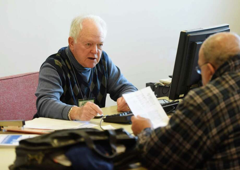 Jacob Schondorf helps a Greenwich resident with his taxes at an AARP clinic in February 2016. The Connecticut General Assembly is considering legislation that would require tax preparers to have a license, with only a few states having such a mandate including New York and California. Photo: Tyler Sizemore / Hearst Connecticut Media / Greenwich Time