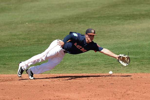 KISSIMMEE, FL - MARCH 15:  Alex Bregman #82 of the Houston Astros dives for a ground ball during the third inning of a spring training game against the Washington Nationals at Osceola County Stadium on March 15, 2016 in Kissimmee, Florida.