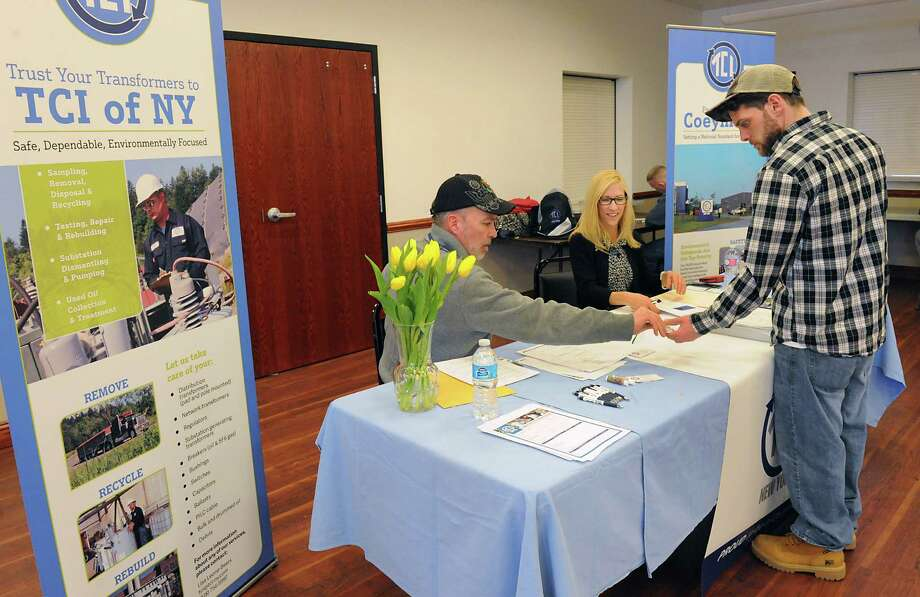 Job seeker Jason Martin, right, talks to representatives John Barr and Bonnie Vandenburgh of TCI as the Port of Coeymans and the Coeymans Industrial Park host a job fair at the Coeymans Fire Department Tuesday, March 15, 2016 in Coeymans, N.Y. (Lori Van Buren / Times Union) Photo: Lori Van Buren / 10035847A