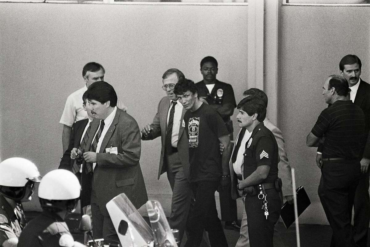 Richard Ramirez, the man police have arrested as the alleged Night Stalker is surrounded by police officers as he walks out of a police station in 1985.