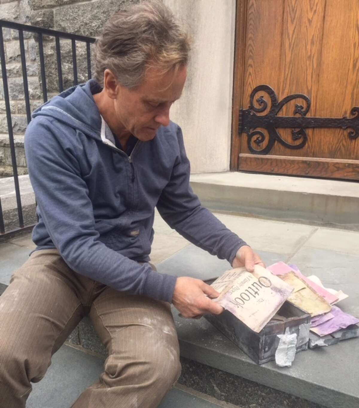 The Rev. Richard S. DenUyl, Jr., the church pastor at First Congregational Church of Greenwich, takes a glimpse into the past after an old time capsule was retrieved.