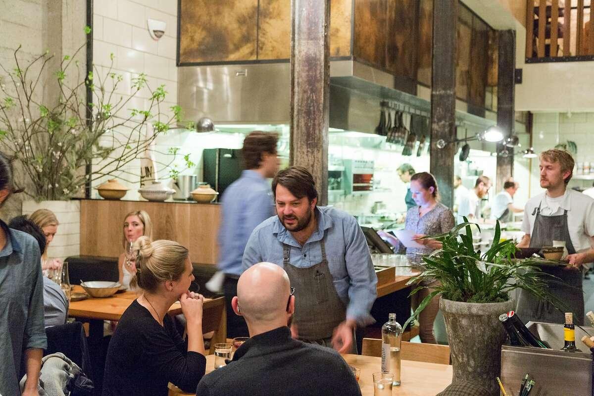 Stuart Brioza (center) runs a dish to a table at the Progress restaurant in S.F. in 2015.