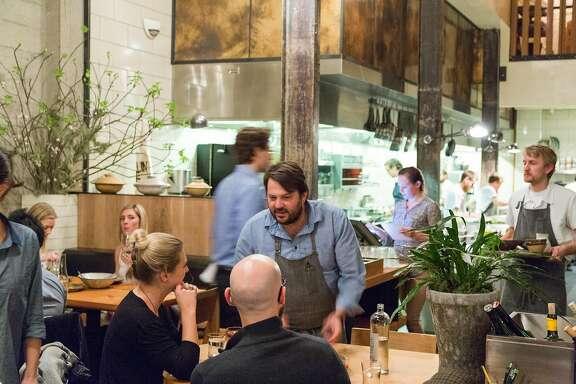 Stuart Brioza runs a dish to a table at The Progress restaurant in San Francisco, Calif., Wednesday, Feburary 4, 2015.
