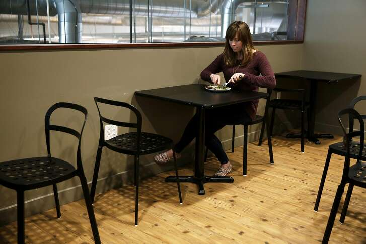 Ashley McCormack of Environmental Working Group eats a salad with salmon at a restaurant down the street from her office in Oakland, California, on Tuesday, March 15, 2016.