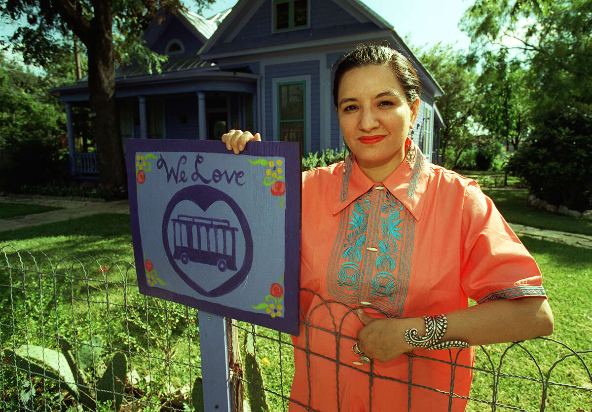 Sandra Cisneros stands in front of her home in King William with a trolley sign on July 7, 1997. When she sold her home in January 2015, it was listed at $995,000.