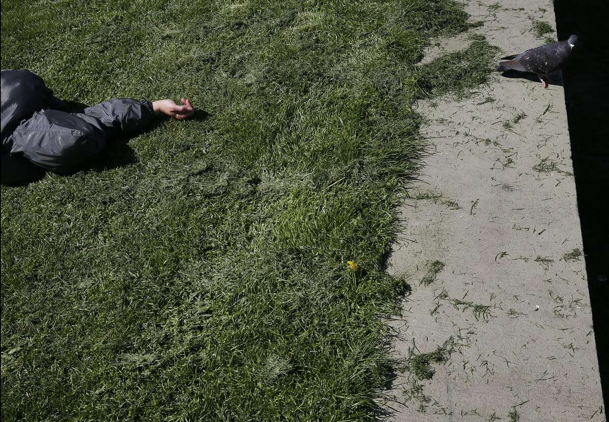 A person sleeps near Civic Center Plaza, one of the sites for a homeless shelter proposed by District 9 Supervisor David Campos March 15, 2016 in San Francisco, Calif.