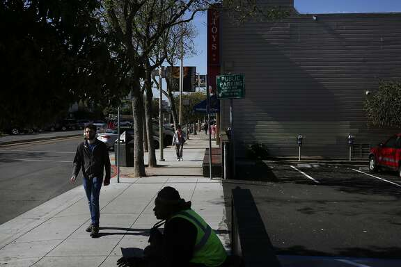 Darnell Williams greets a pedestrian while selling Street Sheets next to a parking lot in the West Portal neighborhood that is the site of a homeless shelter proposed by District 9 Supervisor David Campos March 15, 2016 in San Francisco, Calif.