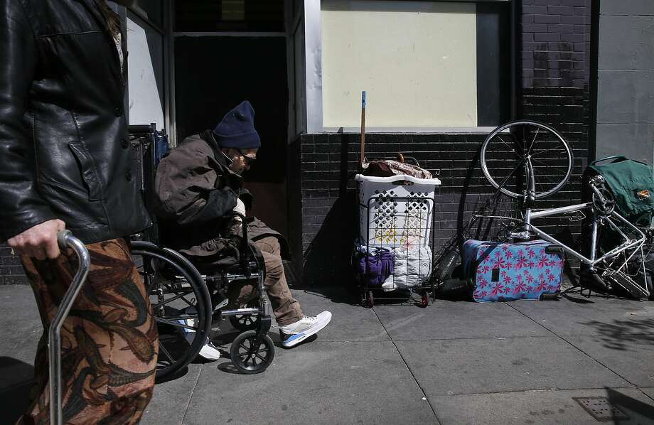 Pedestrians move past someone's possessions on Sixth Street. Un hap piness with home lessness is at its highest point in a decade. Photo: Leah Millis, The Chronicle