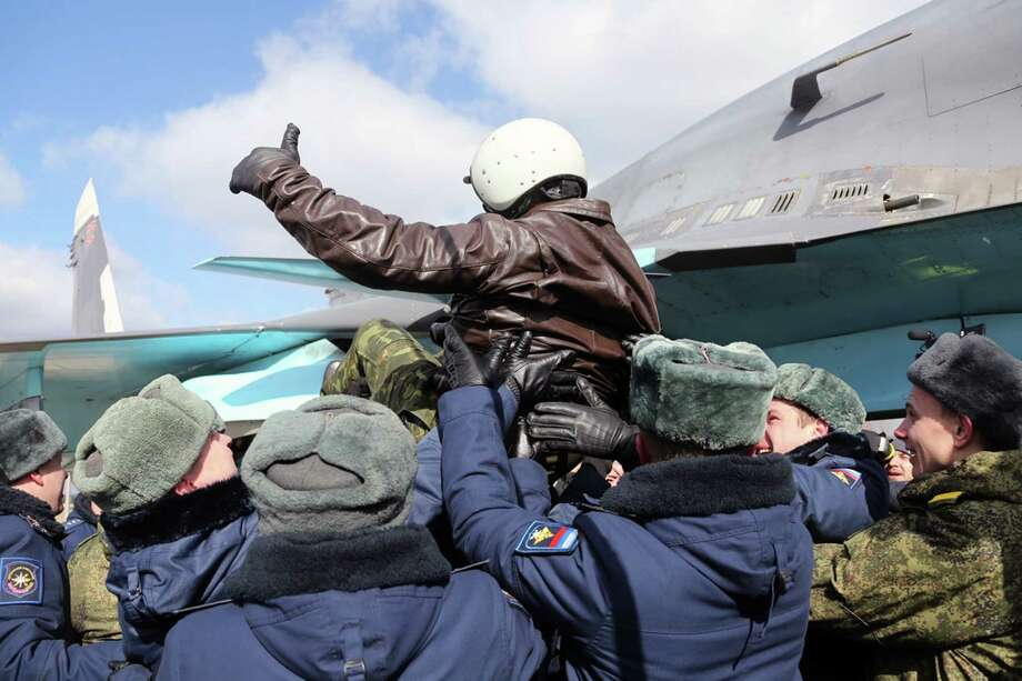 A Russian air force pilot enjoys a welcome on Tuesday during an official ceremony for servicemen returning from Syria. Even senior military commanders appeared surprised by the withdrawal.   Photo: OLGA BALASHOVA, Handout / AFP