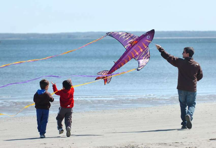 George D'Angelo, of Riverside, plays the Pied Piper with his fish kite as his two sons, Derek, 4, left, and Jake, 3, center, follow along during the annual Kite Flying Festival at Greenwich Point, Saturday afternoon, April 10, 2010.