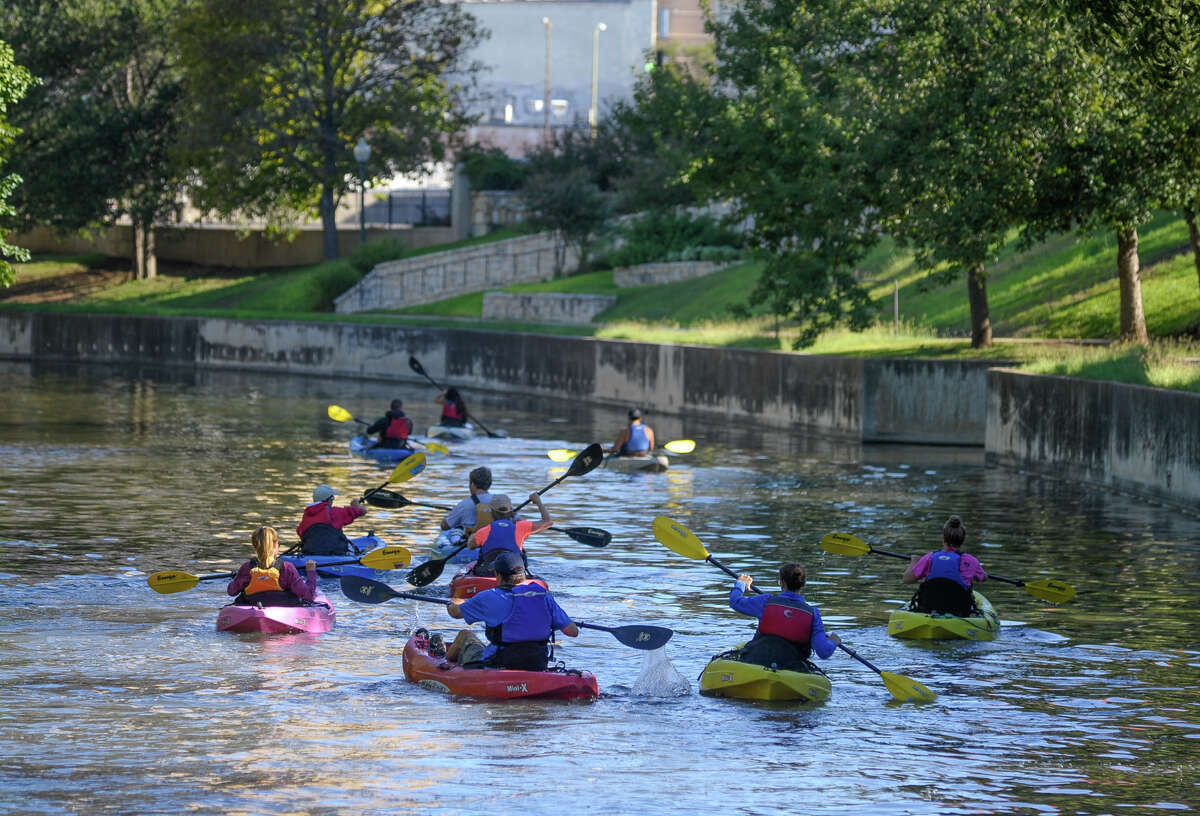 Kayakers paddle in the San Antonio River near the King William Historic District.