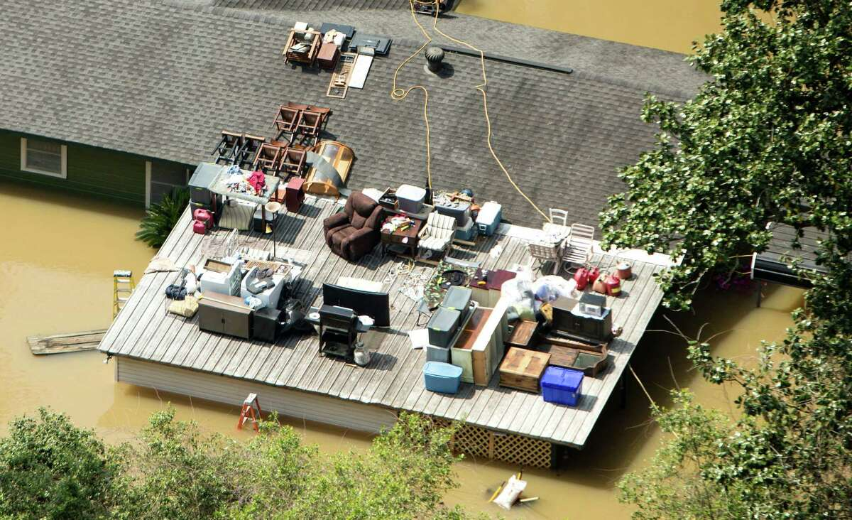 Furniture and other household items are stacked on top of a house in Deweyville, north of Orange, submerged in floodwaters on Tuesday.