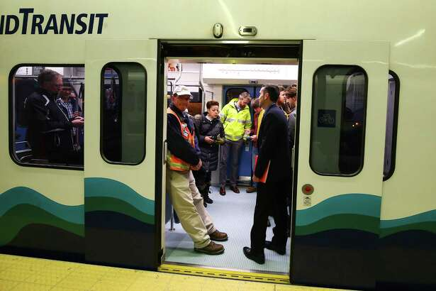 Members of the media and Sound Transit employees board a light rail train during a Sound Transit-hosted first-look ride from the University of Washington station to the Capitol Hill station, Tuesday, March 15, 2016.  Both stations will begin train service Saturday at 10 a.m.