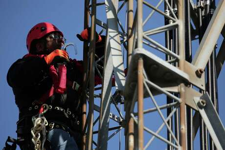 Antonio Crum climbs a cellphone tower while practicing maintenance during a training program in Chicago.