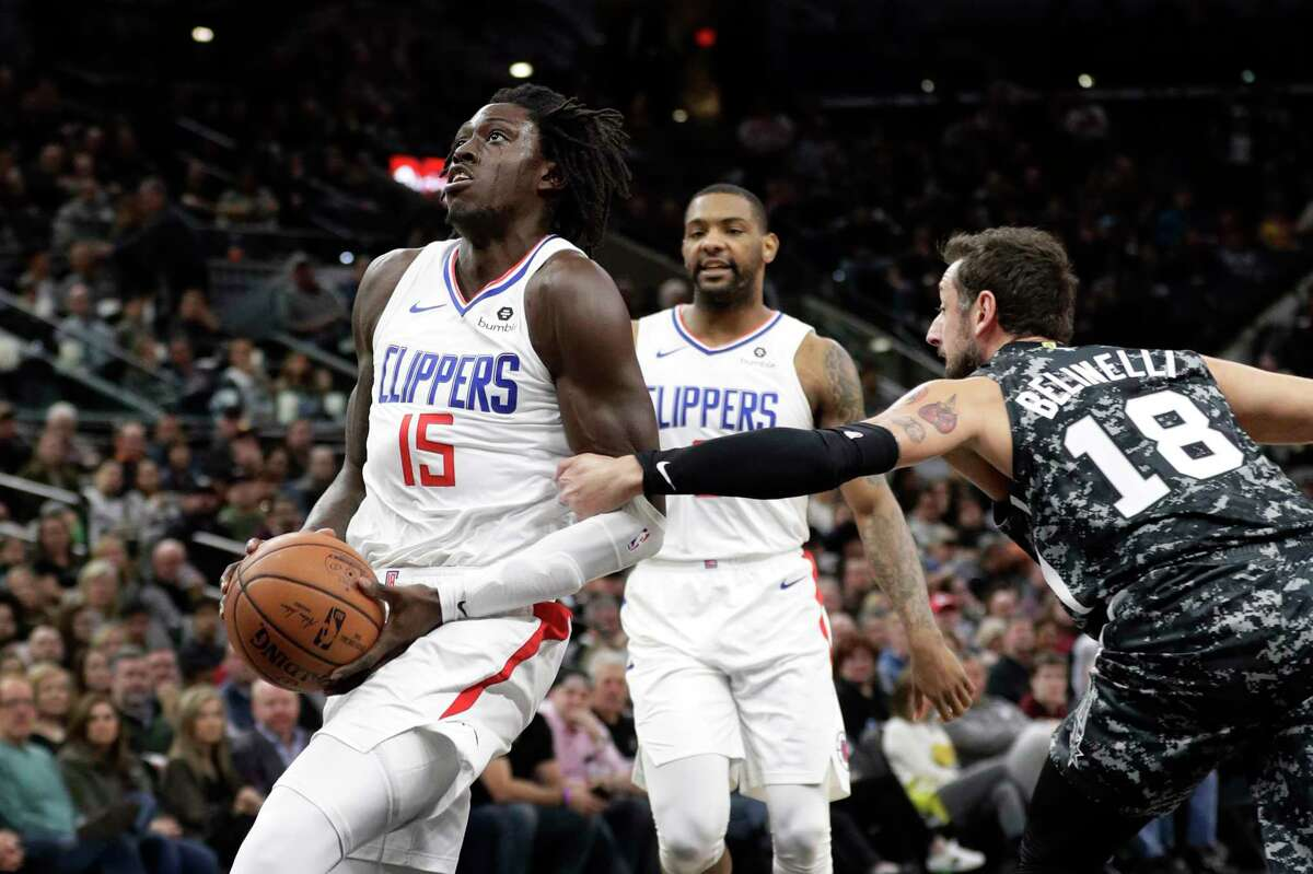 Los Angeles Clippers forward Johnathan Motley (15) is fouled by San Antonio Spurs guard Marco Belinelli (18) while driving to the basket during the first half of an NBA basketball game, Sunday, Jan. 20, 2019, in San Antonio. (AP Photo/Eric Gay)