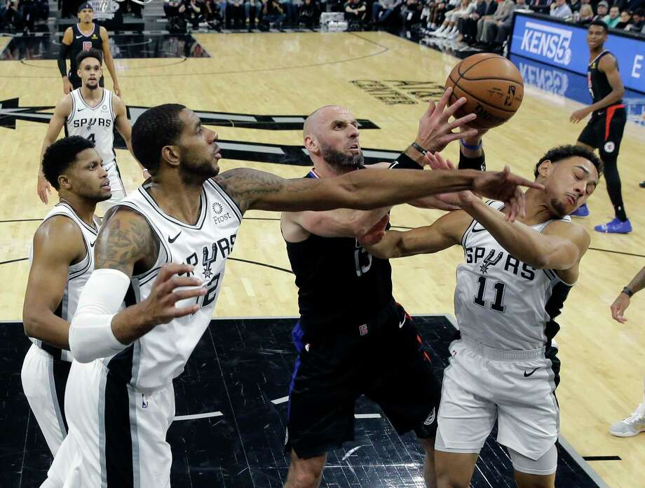 Los Angeles Clippers center DeAndre Jordan, left, loses the ball as he tangles with San Antonio Spurs' Dejounte Murray during the first half of an NBA basketball game, Monday, Dec. 18, 2017, in San Antonio. (AP Photo/Darren Abate) Photo: Darren Abate, Associated Press / FR115 AP