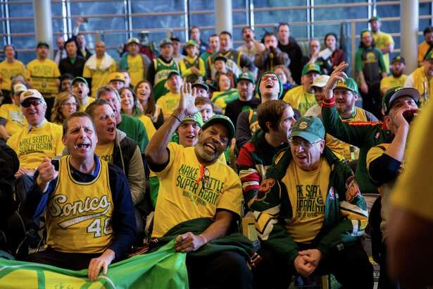 Seattle SuperSonics fan cheer during a gathering before a hearing on the proposed new arena in SoDo, at Seattle City Hall on Tuesday, Mar. 15, 2016.