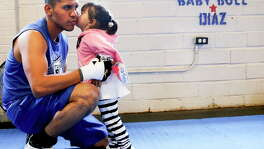 Before a training session, Juan Diaz takes care of the necessary task of taping his gloves and a more enjoyable one in receiving a kiss from daughter Kimberley.