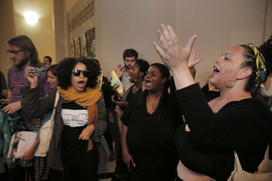 Alicia Bell, right, and several others activists chant outside the Oakland Mayor's office after bout 50 members of the East 12th Coalition disrupted the Oakland City Council meeting at City Hall in Oakland, Calif., on Tuesday, March 15, 2016. The activists who have long opposed the project came up with their own development proposal for the land, only to see it land back in the hands of developer Michael Johnson. Photo: Carlos Avila Gonzalez, The Chronicle