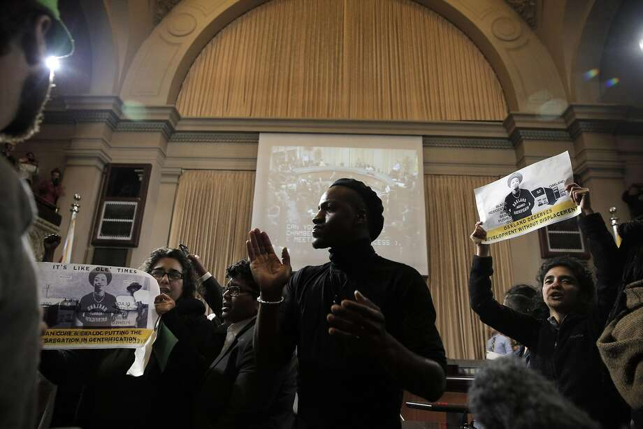 L-R, Activists Dunya Alwan, Sampson McCormick, and Poonam Wahbi, chant in front the dais after about 50 members of the East 12th Coalition disrupted the Oakland City Council meeting at City Hall in Oakland, Calif., on Tuesday, March 15, 2016. The activists who have long opposed a development project on E. 12th Street, came up with their own development proposal for the land, only to see it land back in the hands of developer Michael Johnson. Photo: Carlos Avila Gonzalez, The Chronicle