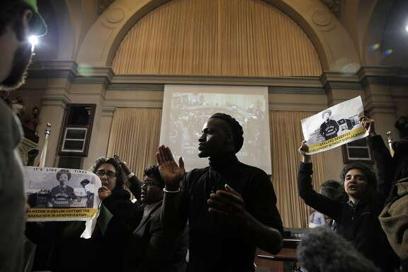 L-R, Activists Dunya Alwan, Sampson McCormick, and Poonam Wahbi, chant in front the dais after about 50 members of the East 12th Coalition disrupted the Oakland City Council meeting at City Hall in Oakland, Calif., on Tuesday, March 15, 2016. The activists who have long opposed a development project on E. 12th Street, came up with their own development proposal for the land, only to see it land back in the hands of developer Michael Johnson.