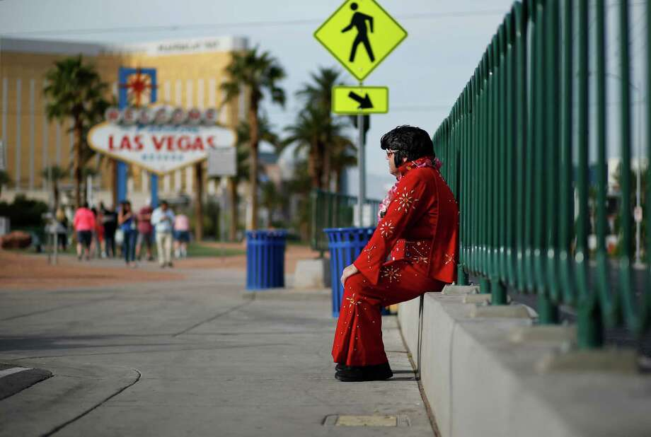 "Ted Payne takes a break from working for tips near the ""Welcome to Las Vegas"" sign. Payne says business has slowed dramatically.  Photo: John Locher, STF"